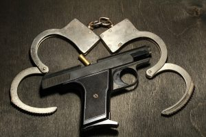 a Gun and Handcuffs Sitting on a Wooden Tabletop